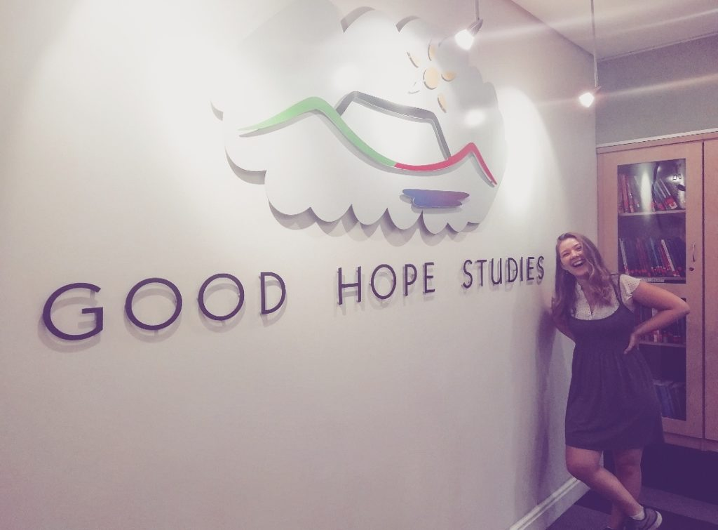 smiling teacher next to Good Hope School logo